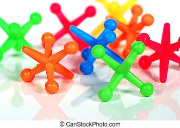 Colorful Toy Jacks - Toy jacks on a white shiny surface.