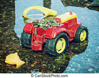 Colorful toy tractor reflected in the water