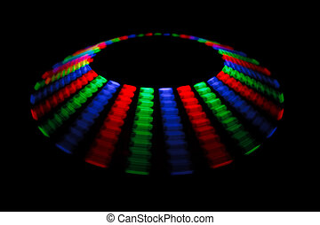 Colorful trace rotating LED in form of a disc on a black background.