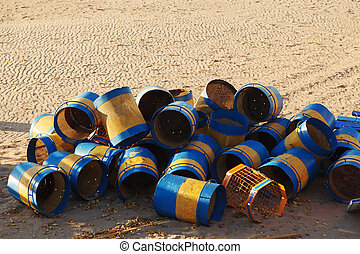 Colorful trash cans stacked on a sandy beach at the end of the season
