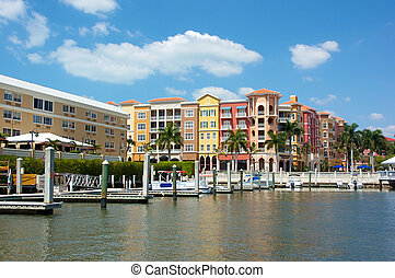 colorful tropical buildings overlooking water and piers -...