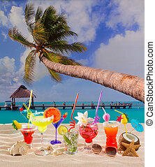 Colorful tropical cocktails at beach on white sand and palm...