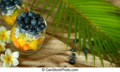 Colorful tropical mix salad in jar. Fresh various kind of raw organic berry and fruit in glass bowl. Healthy vegetarian