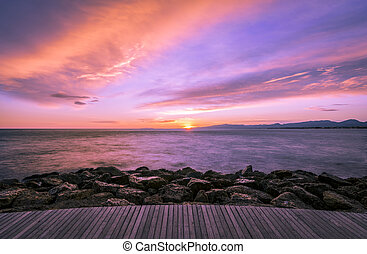 Colorful ultra violet dark sunset over the sea and with a wooden walkway and rocks on the foreground.