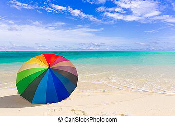 A background of a colorful umbrella on the beach.