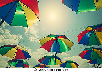 Colorful umbrellas hanging above the street with vintage tone.
