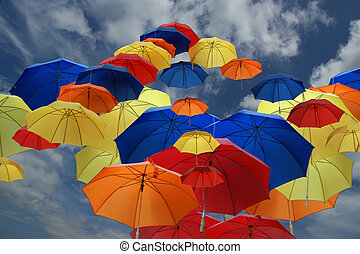 colorful umbrellas on the background of the cloudy blue sky