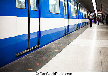 Colorful Underground Subway Train with blurry People on the Platform. Focus is on the door. room for your text.