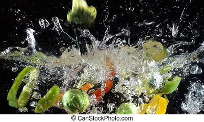 Colorful vegetables falling to water on black background -...