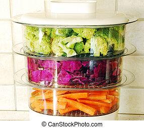green broccoli, magenta cabbage and orange carrots in steamer