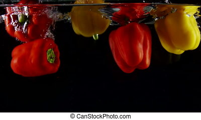 Colorful vegetables sweet bell peppers falls into clear water slow motion