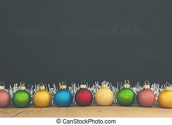 Colorful vintage Christmas baubles on chalkboard