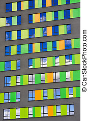 colorful wall of the building with reflective windows in the sky