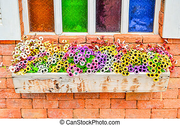 Colorful window on a brick wall.