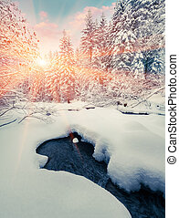 Colorful winter sunrise in the mountain forest with dark water river.