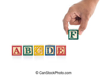 "Colorful wood alphabet blocks and hand holding ""F"" isolated on white"