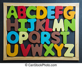 Colorful wooden alphabet on black board