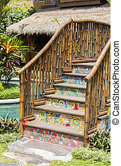 Colorful wooden bridge in a tropical garden next to the swimming pool . Bali, Indonesia