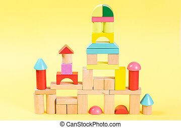 Colorful wooden building blocks on yellow background.