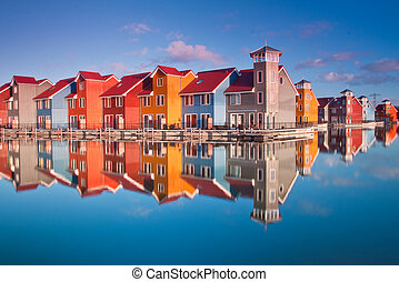 Colorful wooden houses near water in the morning sun