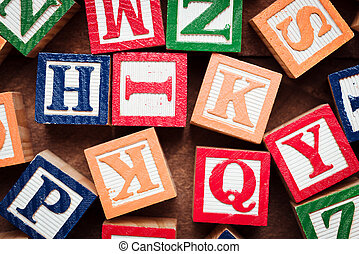Colorful wooden letter blocks making the on brown wood background