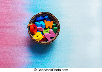 Colorful wooden letters in container on a colorful background