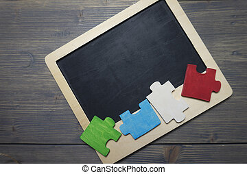 Colorful wooden puzzle pieces on chalk board