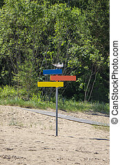 Colorful wooden signpost of directions on a sand beach.