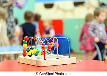Colorful wooden toy stand at table in kindergarten; children...