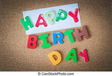 Colorful Wooden word HAPPY BIRTH DAY with piece of White paper on cork board