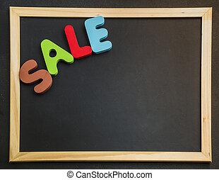 Colorful wooden word Sale on blackboard