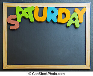 Colorful wooden word Saturday on black board