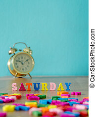 Colorful wooden word SATURDAY on wooden table and vintage alarm clock and background is powder blue. English alphabet made of wooden letter color.