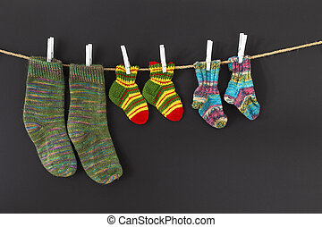 Colorful woolen socks on a rope on black background