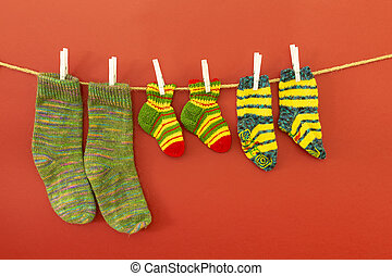 Colorful woolen socks on a rope on red background