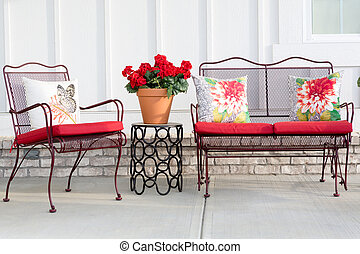 Colorful wrought iron garden furniture with vibrant red...