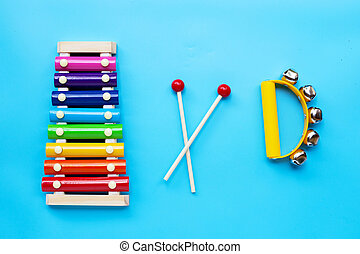 Colorful xylophone with hand bells musical instrument for ringing on blue background.