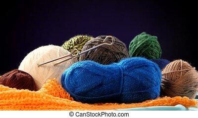 Colorful yarn balls with spokes on orange scarf, black background