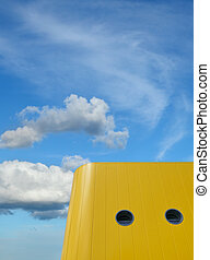 Colorful yellow modern building and blue sky with clouds
