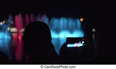 Silhouettes of people who watch, take pictures and shoot videos on smartphones with a bright colored fountain.