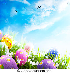 colorido, huevos de pascua, adornado, con, flores, en, el, pasto o césped, en, cielo azul, plano de fondo