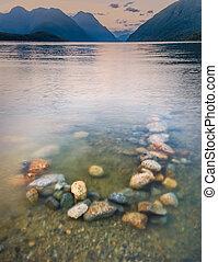 colorido, rocas, en, lago, con, plano de fondo, montañas