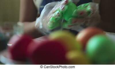 Coloring easter eggs - Woman coloring easter eggs, rack...