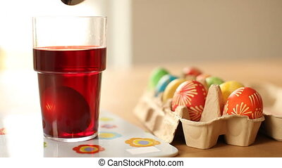 Coloring painted Easter eggs - Removing a painted egg from...