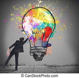 Colors a lightbulb - Businessman color with a spray a...