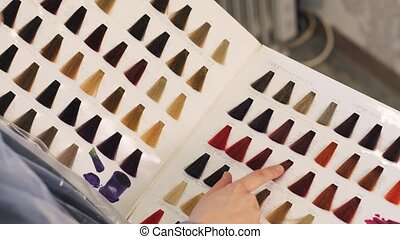 Colors Are Presented Original Hair Color, Blue, Pink, Purple, White on Heavy Cardboard Book in a Beauty Salon, the Girl Holds a Finger on Paint Options and Choose the Hair Color 4k