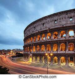 Colosseum at night with colorful blurred traffic lights. Rome - Italy
