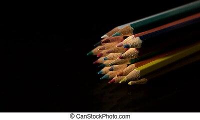 Colour pencils falling on black sur