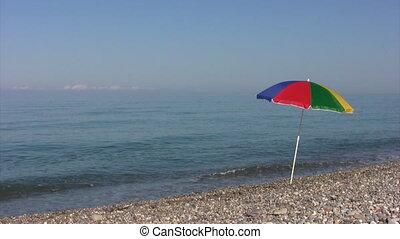 beach umbrella on rocky coast against sea