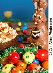 coloured easter eggs in green grass with easter bunny made of chocolate and easter cake on wooden desk in the garden